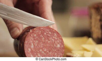 Cutting a piece of sausage. Close-up man hand with knife