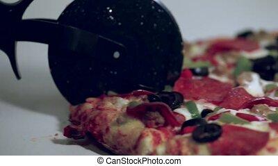 Cutting a Pizza - Pizza cutter cutting a supreme close-up HD...