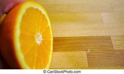 Cutting an orange on a light wooden cutting board, close up video clip