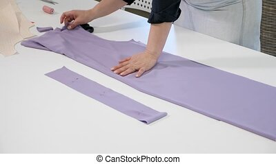 Cutting and sewing products in tailoring business. Dressmaker creating new clothes. Seamstress makes new clothes on table in workshop, hands closeup.
