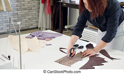 Tailor woman cutting details from fabric works in tailoring workshop business.
