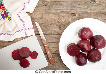 Cutting beetroot on white chopping board over on old wooden table.