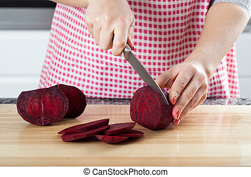 Cutting beetroot - Woman is cutting a beetroot to prepare...
