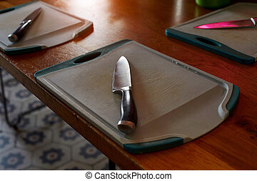 Cutting board with knife on wooden table. Top view