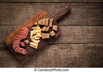 Cutting board with Salami, cheese and bread on dark wooden background