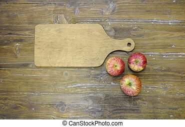 Cutting board with three apples.