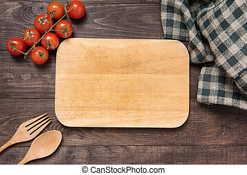 Cutting board with tomato, fork and spoon on wooden background