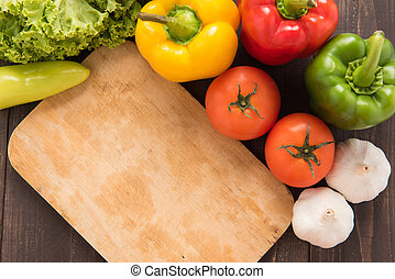 Cutting board with vegetables on wooden background.
