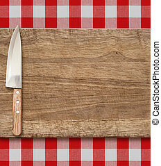 Cutting breadboard and kitchen knife. Cooking set over red gingham tablecloth.