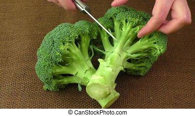 Female hands cutting broccoli in kitchen