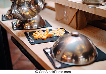 Cutting cheese on a metal bowl with a cap. Breakfast at the Hotel or restaurant.