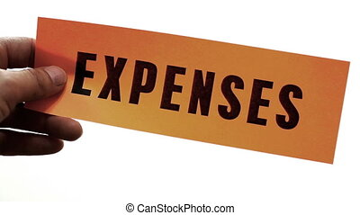 Cutting Expenses Concept - Cutting a bright orange piece of...