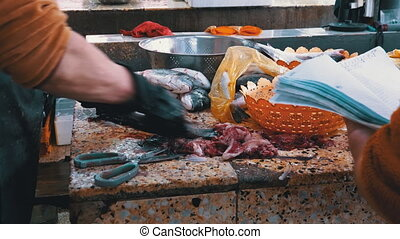 Cutting Fish in Market Stall. Cleaning the inside of marine fish. Woman Vendor Manual cleaning and Cuts Fresh Fish in Market. Gut, Evisceration, Processing, Skinning fish. 4K. Batumi, Georgia.