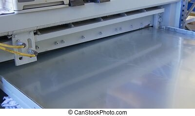 Cutting holes of metal sheets on industrial CNC machine.