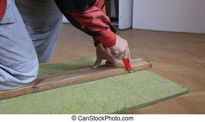 Cutting insulation - Man cutting fiberglass insulation