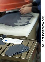 Cutting leather for shoes making.
