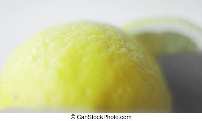 Cutting lemon with a knife. Yellow fresh organic lemon on a white background.