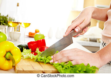 Cutting lettuce - Close-up of young female cutting lettuce...