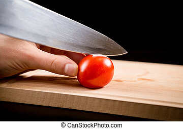 Cutting little red cherry tomato on wooden board