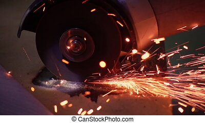 Cutting metal with disc grinder with bright sparks - Cutting...