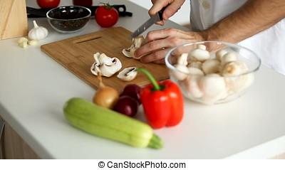 Cutting mushrooms on wooden board