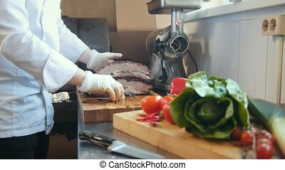 Cutting of a large piece of smoked meat on a wooden board,...