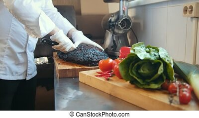 Cutting of a large piece of smoked meat on a wooden board