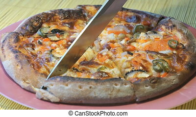 Cutting of pizza into slices using a steel knife