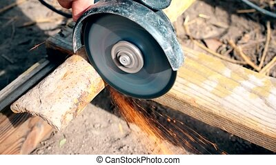 Cutting old rusted iron pipe with an angle grinder outdoors