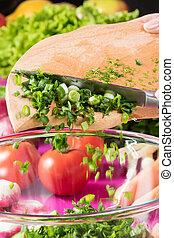 Cutting onion into a salad