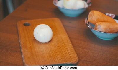 Cutting Onion with Knife into Two Parts on a Cutting Board in the Home Kitchen. Slow Motion