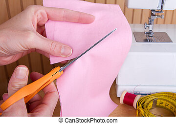 cutting out fabric with scissors