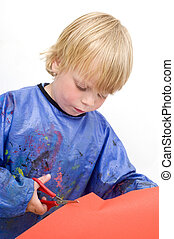 Child cutting a sheet of red paper with a pair of scissors