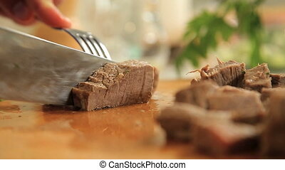 Cutting peace of boiled beef meat on a wooden cutting board