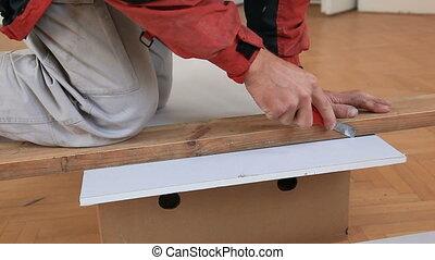 Cutting plasterbord - Worker cutting gypsum board