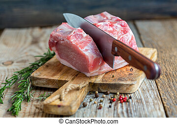 Cutting pork loin. - Piece of pork loin, pepper and rosemary...