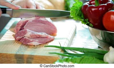 Cutting pork meat - Women hands cutting fresh pork meat in...