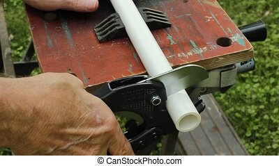 cutting pvc pipe - using a ratchet toll to cut a piece of...