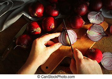 cutting red onions with knife on cutting board