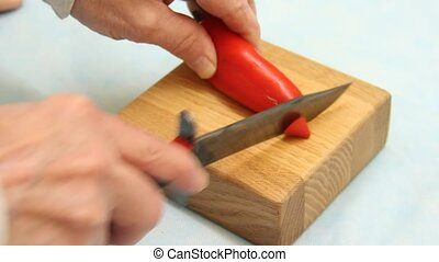 cutting red pepper - chef cutting a red pepper on a board
