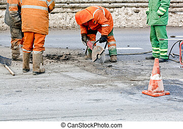 Cutting road works with hydraulic driven angle grinder,...