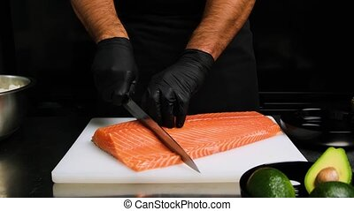 Cutting Salmon fillet in large pieces. Chef cutting Salmon on to big pieces on white desk