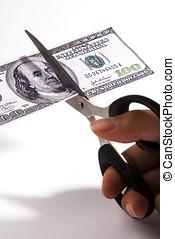 Cutting Spending - Scissors cutting an one hundred dollar...