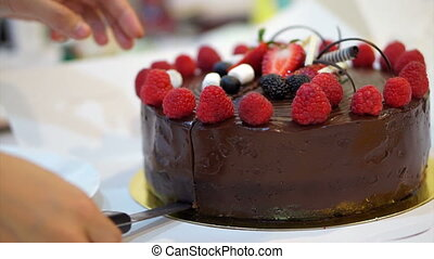 cutting strawberry chocolate cake