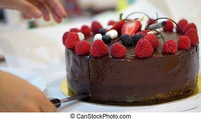 cutting strawberry chocolate cake