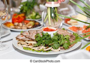 Cutting the meat, tongue, parsley and sauce on a white plate Close-up