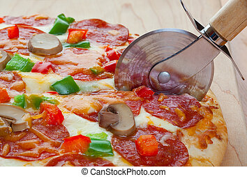 Cutting The Pizza - A deluxe pizza, fresh from the oven, ...