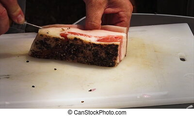 Cutting the skin off a bacon piece - A hand held, medium...