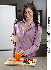 Young woman in a kitchen preparing vegetable, cutting a orange bell pepper with tomato and cucumber slice on the side