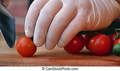 Cutting tomato behind fresh vegetables